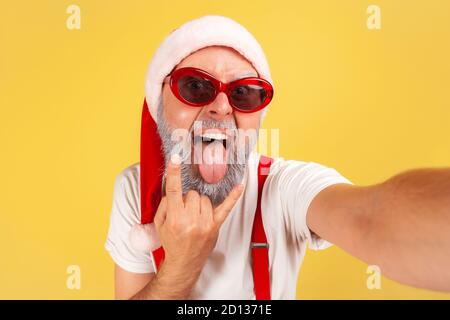 Extremely excited crazy man in santa claus hat and sunglasses fooling faces looking at camera, elderly blogger having fun showing rock gesture. Indoor