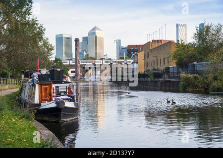 London, Hackney. Narrow Boats on the Regent's Canal with the towers of the Canary Wharf financial district in the distance - Stock Photo