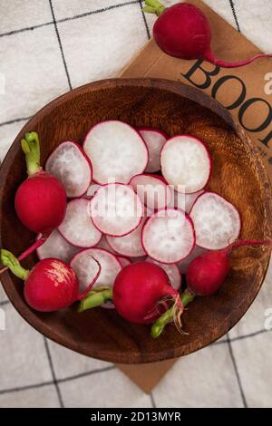 Red radish whole and cut into slices on a wooden plate against a checkered tablecloth. Food photo for ecomarket.