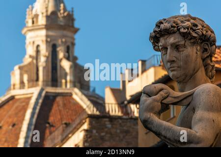 the statue of Michelangelo's David with the cathedral dome of Florence in the background, shot from piazza della Signoria - Florence (Italy) - Stock Photo