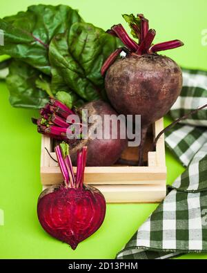 Beets whole and cut in close-up with tops on a green background. - Stock Photo
