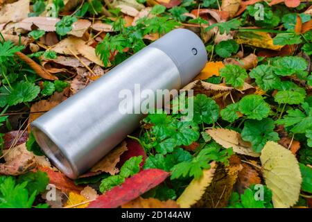 A deodorant thrown out on the lawn in an aluminum can lies on the grass with autumn leaves