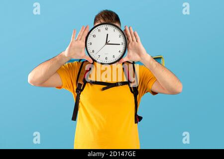 Time to travel concept. Young man with camping equipment holding clock in front of his face over blue studio background - Stock Photo