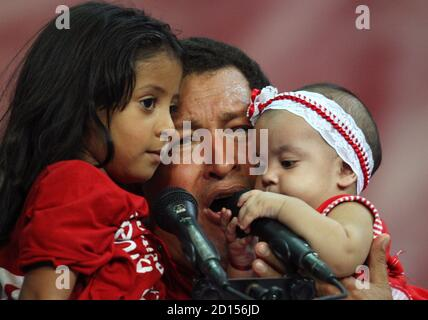 Venezuelan President Hugo Chavez holds up supporters' children as he speaks to members of the United Socialist Party of Venezuela (PSUV) ahead of Sunday's elections in Caracas November 18, 2008. Venezuelans go to the polls on November 23 to elect state governors and city mayors. REUTERS/Jorge Silva (VENEZUELA)