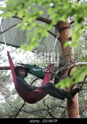 An activist from the environmental organisation 'Robin Wood' sits in a tree in a sealed-off forest area called 'Bannwald' as construction works on a new runway near Frankfurt's Rhine-Main airport started September 11, 2005. Police expect protesters and environmental activists against the extension of the airport.  vk/TY - Stock Photo