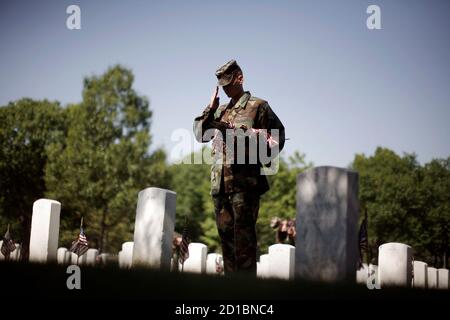 U.S. Air Force Airman 1st Class William Banton, of Roanoke, Virgina, salutes a grave as he places a U.S. flag at each gravestone inside the Arlington National Cemetery, May 24, 2007. Hundreds of members of the U.S. armed forces planted flags at each of the thousands of headstones in the cemetery on Thursday, ahead of Memorial Day on May 28.   REUTERS/Jason Reed   (UNITED STATES)