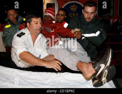 A would-be immigrant is carried by members of the Spanish Civil Guard and Red Cross after arriving at the port of Almeria November 16, 2007. They were intercepted off the southern Spanish coast as they were heading to European soil from Africa, authorities said. REUTERS/Francisco Bonilla (SPAIN) - Stock Photo