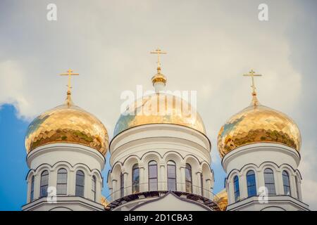 Golden domes, cupolas with Eastern Orthodox crosses on a white Church against a blue sky with clouds
