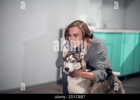 A smiling girl hugging her pet dog in a vet clinic, they are posing for a picture. - Stock Photo