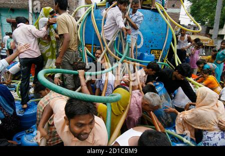 Residents of Sanjay Colony, a residential neighbourhood, scramble to collect water from a tanker provided by the state-run Delhi Jal (water) Board in New Delhi June 30, 2009. Delhi Chief Minister Sheila Dikshit has given directives to tackle the burgeoning water crisis caused by uneven distribution of water in the city according to local media. The board is responsible for supplying water in the capital. REUTERS/Adnan Abidi (INDIA SOCIETY ENVIRONMENT)