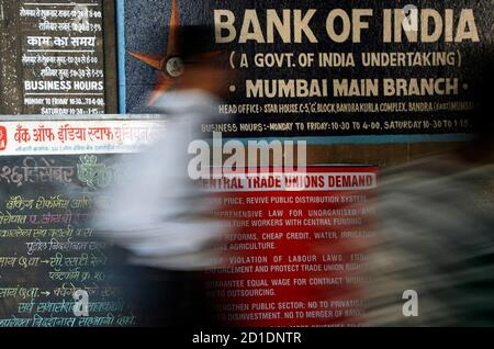A man walks in front of a banner outside a state-run bank during a strike in Mumbai December 16, 2009. About 400,000 bank employees went on strike on Wednesday to protest merging state-owned banks, partially affecting cash transactions and clearing operations, a bank union official said. REUTERS/Arko Datta (INDIA - Tags: BUSINESS)