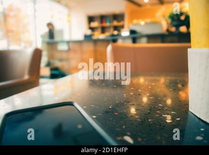 Modern blurred coffee shop Scene. Phone and coffee cup on table as foreground. Soft blurred sofa chair, bar / counter shelves and window front in the
