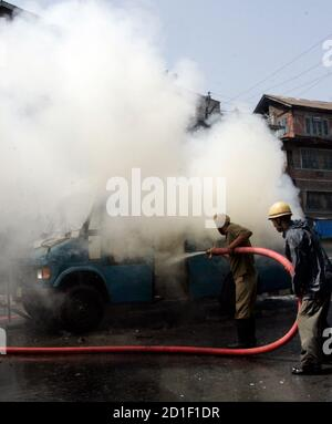 Firefighters douse a fire on a police vehicle during a protest in Srinagar July 8, 2009. Indian police fired shots into the air and used tear gas to disperse hundreds of angry demonstrators who torched police vehicle and pelted stones in Kashmir's main city protesting against the death of a student who was killed by police after his arrest, residents said. Police however denied the charge and said the 20-year-old student, Asrar Ahmad, was murdered by unidentified criminals. Protesters also burned tyres, brought traffic to a halt and forced shops and businesses to shut down in the heart of Srin - Stock Photo