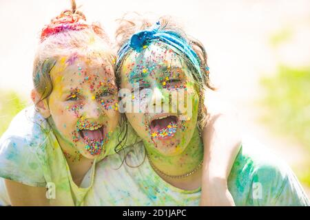 Funny girls with painted color tongue. Children draws paints. Kids friends celebrating Holi festival. - Stock Photo