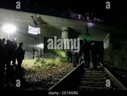 German police officers remove anti-nuclear activists from the German environmental organisation Robin Wood hanging from ropes over a railway track in Oldendorf, between Lueneburg and Dannenberg November November 10, 2008. The controversial shipment of eleven Castor containers with spent German nuclear fuel arrived in Dannenberg on Monday and will be loaded onto trucks before transportation to the nearby Gorleben intermediate storage facility in northern Germany after it left the French reprocessing plant of La Hague on Friday. The banners read, 'love' (L) and 'Stop Castor'. REUTERS/Christian C - Stock Photo
