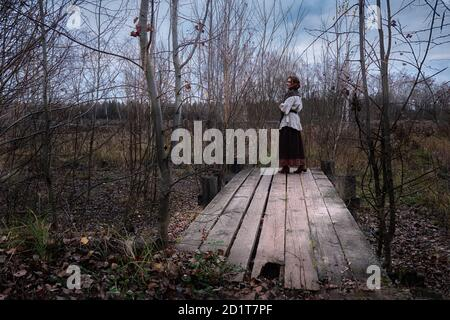 A girl dressed in a vintage dress stands tall on an old wooden platform of boards. A woman by an old pond overgrown with reeds and bushes