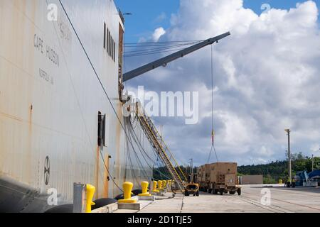 201004-N-ER806-1030  APRA HARBOR, Guam (Oct. 4, 2020)   Sailors from Task Group 75.2 utilize their cargo handling capabilities to onload U.S. Army vehicles onto the roll-on/roll-off cargo ship M/V Cape Hudson (T-AKR 5066) at Naval Base Guam. Task Force 75 is 7th Fleet's primary expeditionary task force and is responsible for the planning and execution of maritime security operations, explosive ordnance disposal, diving, engineering and construction, and underwater construction throughout the Indo-Pacific region. (U.S. Navy photo by Mass Communication Specialist 2nd Class Nick Bauer) - Stock Photo