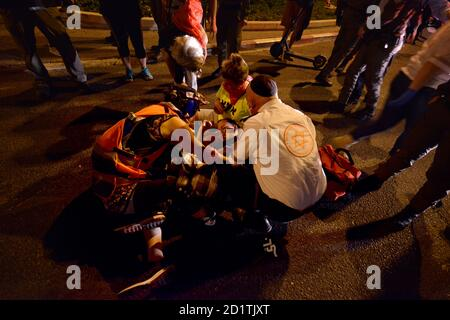 2.10.2020 Tel Aviv, Israel. Protest against Prime minister Netanyahu and second Coronavirus lockdown. An injured protestor who was run over by a police horse is getting medical treatment in the police detention coral on LaGardia street in Tel Aviv.