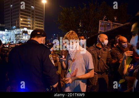 2.10.2020 Tel Aviv, Israel. Protest against Prime minister Netanyahu and second Coronavirus lockdown. Protestor getting a fine for not keeping 2m distance in the police corral.