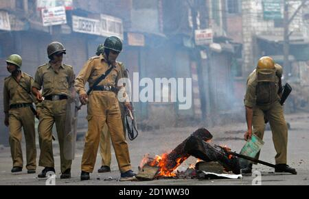 Indian policemen walk past a fire during a protest in Srinagar July 8, 2009. Indian police fired shots into the air and used tear gas to disperse hundreds of angry demonstrators who torched police vehicle and pelted stones in Kashmir's main city protesting against the death of a student who was killed by police after his arrest, residents said. Police however denied the charge and said the 20-year-old student, Asrar Ahmad, was murdered by unidentified criminals. Protesters also burned tyres, brought traffic to a halt and forced shops and businesses to shut down in the heart of Srinagar, Kashmi - Stock Photo