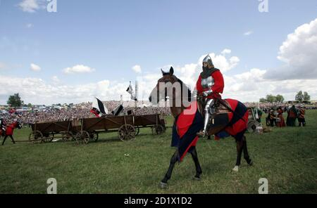 An amateur actor rides his horse before a re-enactment of the battle at Grunwald, which took place 1410 between Teutonic order knights and Polish and Lithuanian knights, in Grunwald, north Poland July 15, 2006. REUTERS/Katarina Stoltz (POLAND) - Stock Photo