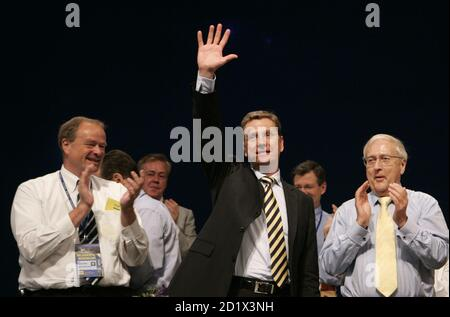 Guido Westerwelle (C) party leader of Germany's Free Democratic Party (FDP) waves after his speech as general secretary Dirk Niebel (L) and deputy party leader Rainer Bruederle (R) applaud during the general party meeting in the southern German city of Stuttgart June 15, 2007.    REUTERS/Alex Grimm  (GERMANY) - Stock Photo