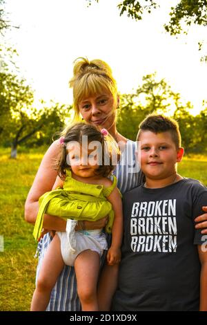 Grandmother with her grandchildren. Granddaughter and grandson in autumn or summer park. Family outdoor portrait.