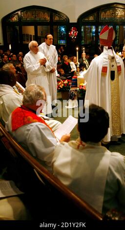 Married deacons, Dominic Riccio (L) and Raymond Grosswirth, stand at the beginning of their ordination ceremony conducted by excommunicated Roman Catholic Archbishop Emmanuel Milingo (R) at the Trinity Reformed Church in West New York, New Jersey, December 10, 2006.  Milingo ordained the two married clergymen as priests on Sunday, defying the Vatican over the controversial issue of celibacy within the priesthood. REUTERS/Jeff Zelevansky (UNITED STATES) - Stock Photo