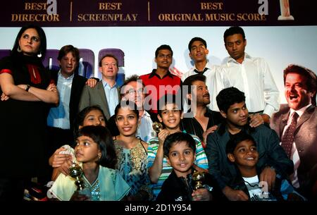 The cast and crew of film 'Slumdog Millionaire', including child actors Rubina Ali (front left holding Golden Globe) and Ayusha (front centre holding Golden Globe), pose during a news conference in Mumbai January 20, 2009. British director Danny Boyle's Golden Globe award-winning film will be released in India on January 23. REUTERS/Punit Paranjpe (INDIA)