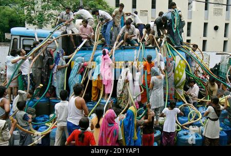 Residents of Sanjay Colony, a residential neighbourhood, crowd around a water tanker provided by the state-run Delhi Jal (water) Board to fill their containers in New Delhi June 30, 2009. Delhi Chief Minister Sheila Dikshit has given directives to tackle the burgeoning water crisis caused by uneven distribution of water in the city according to local media. The board is responsible for supplying water in the capital. REUTERS/Adnan Abidi (INDIA ENVIRONMENT SOCIETY)