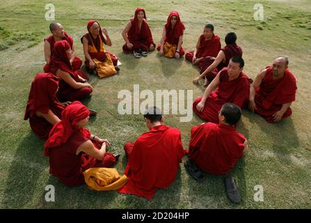 Tibetan monks wait for their vehicle after a prayer meeting for those who lost their lives during China's crackdown on protests in Tibet, at the memorial of Mahatma Gandhi in Rajghat, New Delhi, March 29, 2008. REUTERS/Adnan Abidi (INDIA) - Stock Photo
