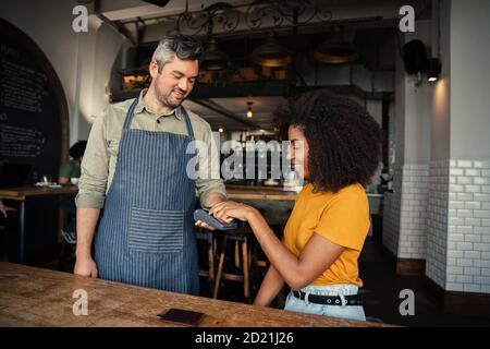 Beautiful ethnic woman tapping card making payment for coffee to handsome waiter in trendy cafe.