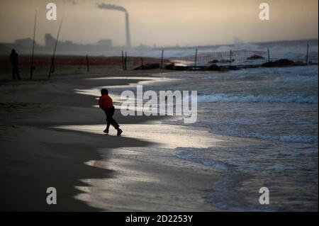 An Israeli boy plays on a rainy day at Nitzanim beach near the southern city of Ashkelon October 30, 2009. REUTERS/Amir Cohen (ISRAEL ENVIRONMENT SOCIETY)