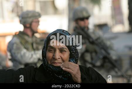 A woman walks past U.S. soldiers standing guard at the newly restored Abu Nawas road in Baghdad November 18, 2007.   REUTERS/Mohammed Ameen   (IRAQ) Stock Photo