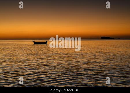 Sunrise over the Mediterranean sea with a small fishing boat Stock Photo