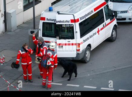 Members of the emergency rescue services gather with a rescue dog near to the collapsed building of the town archive of the German city of Cologne, March 3, 2009. More than 200 rescue workers rushed to the scene in the south of the city after the collapse of the multi-storey building, which German media said may have been sparked by work on an underground train line.  At least one person was injured and possibly others are trapped inside, a Cologne police spokesman said, adding the cause for the collapse was still unclear. In background is Cologne Cathedral.     REUTERS/Ina Fassbender   (GERMA - Stock Photo