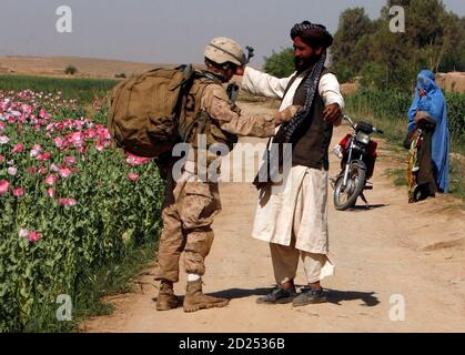 A U.S. Marine from Lima company 3rd Battalion 6th Marine Regiment searches an Afghan man as they patrol in Karez-e-Sayyidi, in Helmand province, April 5, 2010. REUTERS/Asmaa Waguih  (AFGHANISTAN - Tags: CIVIL UNREST MILITARY CONFLICT) - Stock Photo