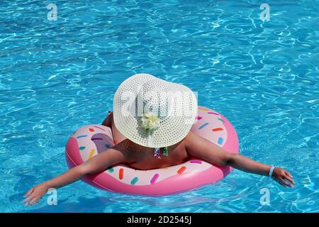 Woman in hat and bikini swimming on inflatable donut ring in the pool. Beach vacation, relax and leisure concept - Stock Photo