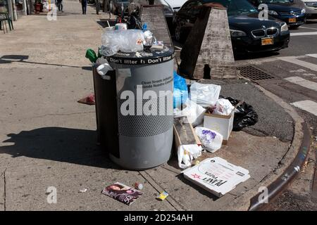overflowing public waste bin or trash can on a corner in new york city with the words don't litter written on it - Stock Photo