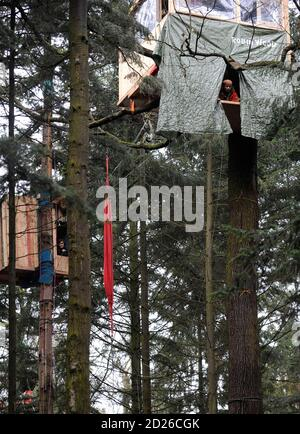 Activists of environmental organization Robin Wood observe police activities from their tree houses, built in protest against the clearing of a wooded area for a new runway for the airport, in Frankfurt January 20, 2009. Some of the demonstrators have been living in the wooded area slated for clearing as a form of protest for the past 6 months. REUTERS/Kai Pfaffenbach (GERMANY) - Stock Photo
