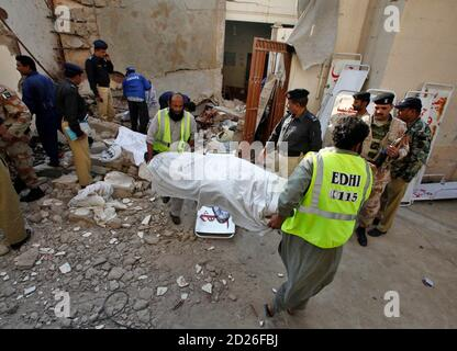 Security officials survey while rescue workers shift a dead body at a collapsed house following an explosion in Karachi January 8, 2010. At least six people were killed in the Pakistani city of Karachi on Friday when explosives being stored in an suspected militant hideout apparently went off accidentally, police said. REUTERS/Akhtar Soomro   (PAKISTAN - Tags: CIVIL UNREST CRIME LAW POLITICS)
