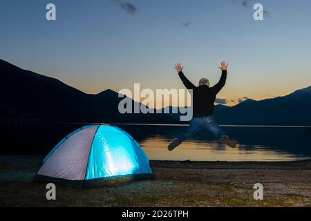 Man Jumping and an Illuminated Tent on Alpine Lake Maggiore with Mountain in Dusk in Ascona, Switzerland. - Stock Photo