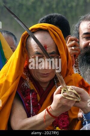 Tibetan spiritual leader Dalai Lama holds a sword presented to him by a representative of India's Sikh community, after a prayer meeting for those who lost their lives during China's crackdown of protests in Tibet, at the memorial of Mahatma Gandhi in Rajghat, New Delhi March 29, 2008. REUTERS/Adnan Abidi (INDIA) - Stock Photo