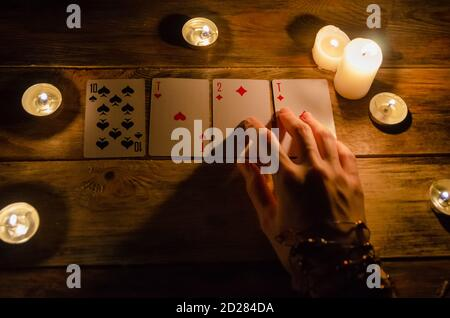 Hands of a fortune teller and cards on the table, around lit candles in the dark on a wooden table. concept of divination, magic. view top