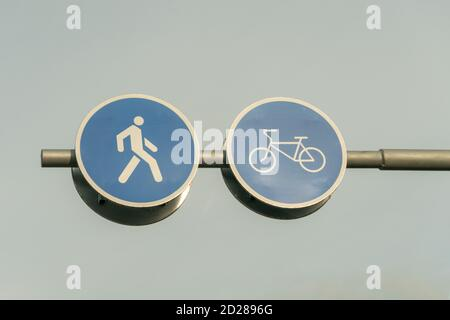 Two road signs side by side for pedestrians and cyclists close up against the sky and tree branches - Stock Photo