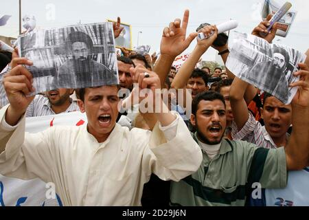 Demonstrators hold pictures of Saleh al-Jezani as they chant slogans demanding his release from the custody of British forces, during a rally in Basra, 550km (340 miles) southeast of Baghdad May 4, 2007.  Al-Jezani, a member of the Sadr political party was arrested by the British forces during a raid in Sadr party headquarters in Basra two days ago, protesters said.        REUTERS/Atef Hassan     (IRAQ)
