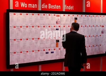 A man read job offers during the first day of the 'Hannover Messe' industrial trade fair in Hanover April 19, 2010. The world's leading fair for industrial technology, with about 4,800 exhibitors from 63 nations, runs till April 23 with Italy as this year's partner country. The slogan reads: Where you can find the best!.     REUTERS/Tobias Schwarz     (GERMANY - Tags: SCI TECH)