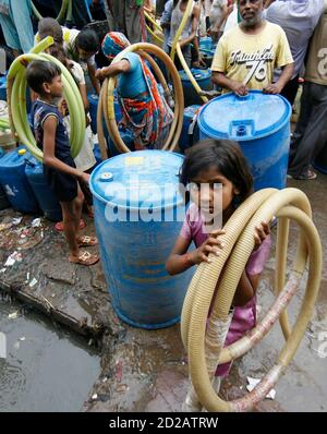 Residents of Sanjay Colony, a residential neighbourhood, carry pipes as they leave after filling their containers from a water tanker provided by the state-run Delhi Jal (water) Board in New Delhi June 30, 2009. Delhi Chief Minister Sheila Dikshit has given directives to tackle the burgeoning water crisis caused by uneven distribution of water in the city according to local media. The board is responsible for supplying water in the capital. REUTERS/Adnan Abidi (INDIA SOCIETY)