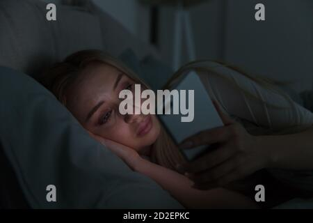 Portrait of young sleepy tired woman lying in bed under the blanket using smartphone at late night, can not sleep/ Insomnia, nomophobia, sleep disorde