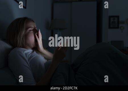 Young sleepy tired woman lying in bed, using smartphone, covering mouth with hand and yawning, eyes closed, can not sleep/Insomnia, nomophobia, sleep